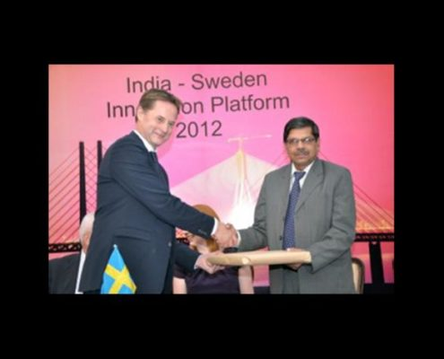 An Indian and a Swedish man shaking hands. Photo.