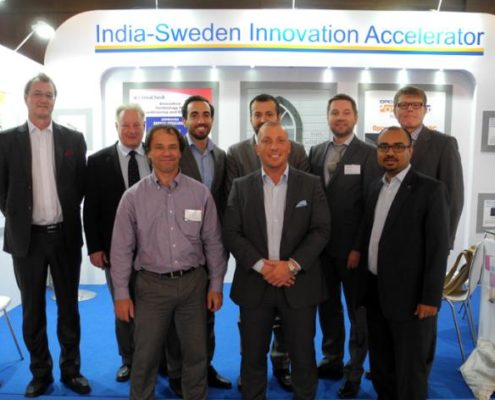 Nine men at the Innovations Accelerator stand. Photo.