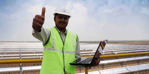 "A man next to a solar power plant, doing a ""thumbs up"". Photo."