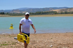 Henrik Johansson carrying a yellow water pump. Photo.