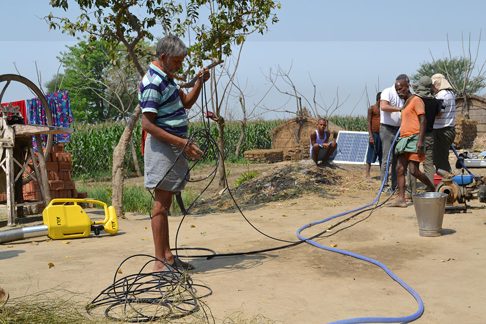 People handling electric cables and a hose. Photo.