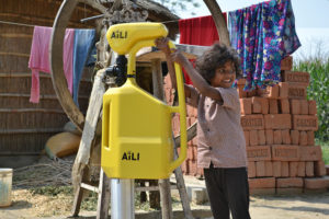 Indian child and yellow water pump. Photo.