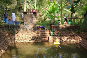 Yellow water pump in a small pond. Photo.