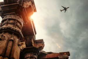 Airplane in the sky above ancient Indian building. Photo.