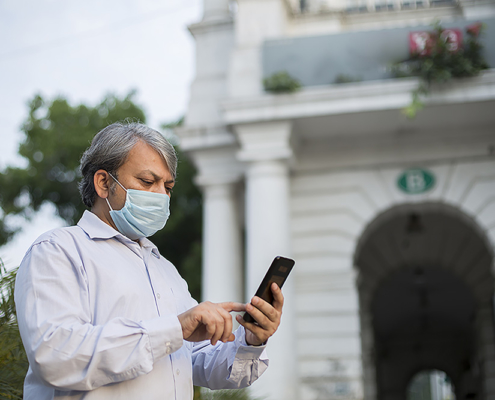 Indian man wearing face mask. looking at a cellphone. Photo.