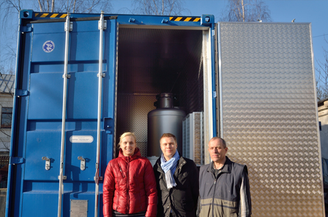 One woman and two men standing in front of technical equipment. Photo.