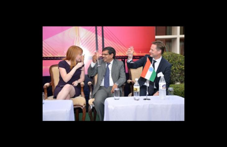 A woman and two men raising their glasses. Photo.