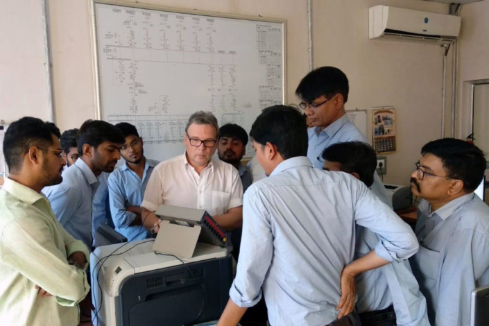 Swedish man demonstrates equipment to ten Indian men. Photo.