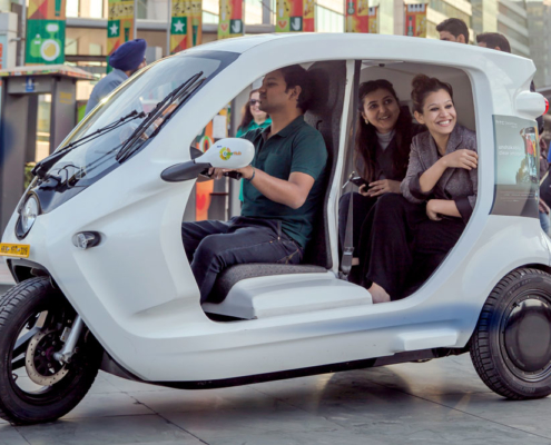 Three people riding in a small electric vehicle. Photo.