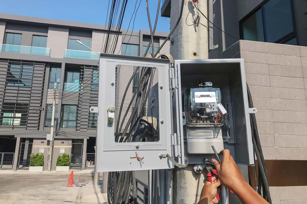 Electric meter and two hands working on it. Photo.