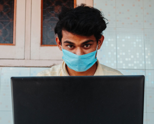 Indian man wearing a face mask, working on a laptop. Photo.