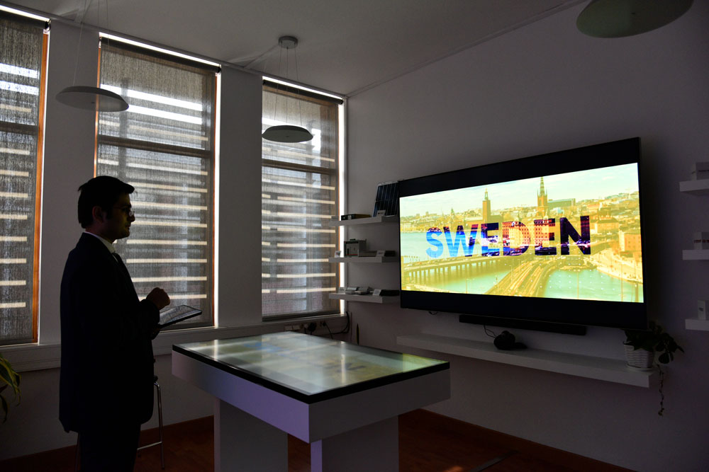 A man watching a big screen in the showroom. Photo.